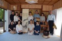 売茶翁が龍律寺7代梁和尚に贈った掛軸の前でスタッフ勢揃い。翁は25年ぶりの龍律寺です